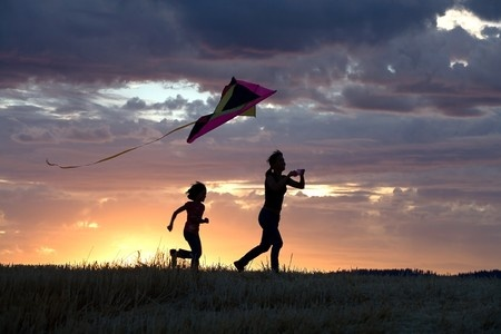 happy people running outside with a kite