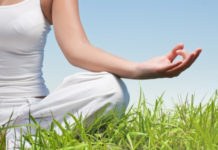 woman meditating in grass